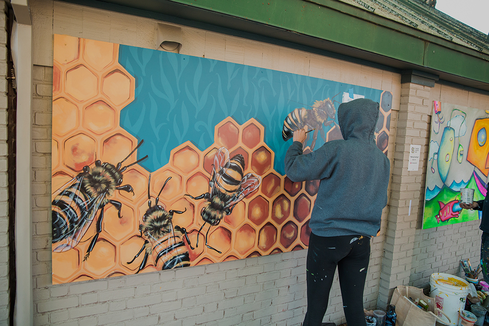Sophy Tuttle painting a mural in Salem, MA