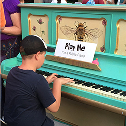 a boy playing a painted piano