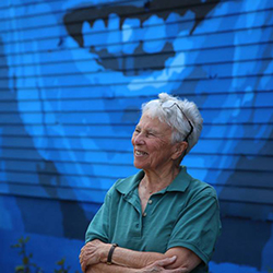 Marion Stoddart standing in front of a mural of her in Fitchburg