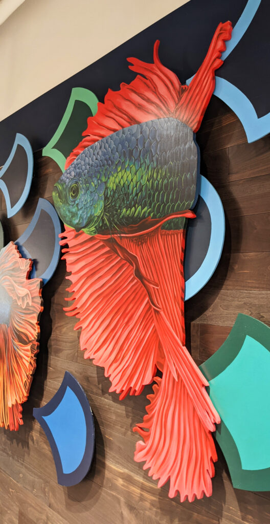 A detail of a cut out fish realistically painted by Sophy Tuttle